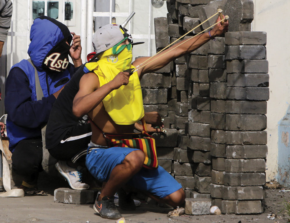 An anti-government demonstrator uses a slingshot during clashes with riot police at a barricade in the town of Masaya.  (Photo: INTI OCON/AFP/Getty Images)