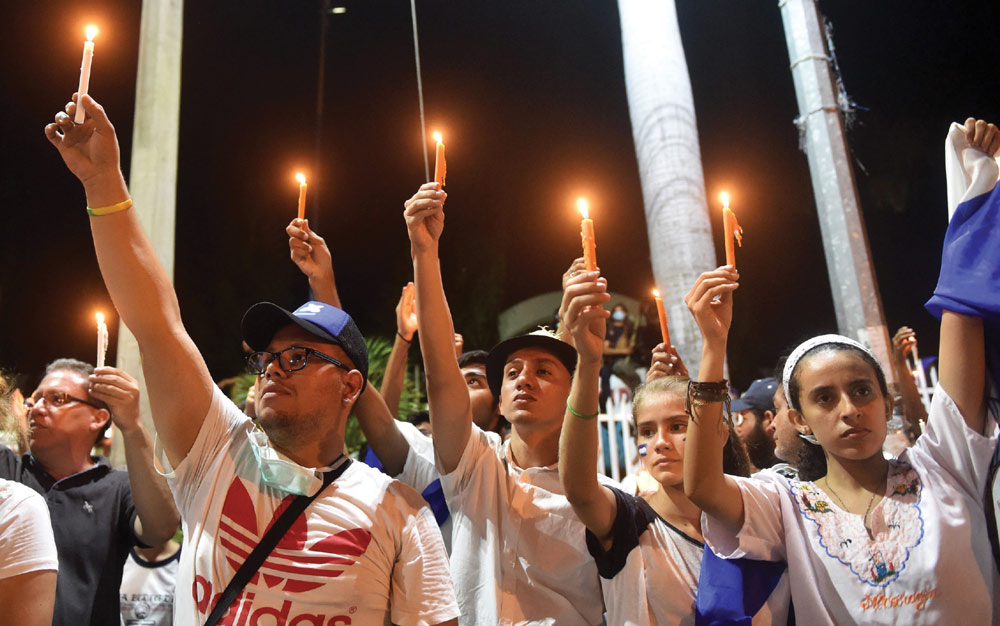 """Students light candles during vigil after taking part in the """"Walk for Peace and Dialogue"""" in Managua, where many demand Nicaraguan President Daniel Ortega and his wife Vice-President Rosario Murillo step down. Ortega has been under pressure to step down after announcing, then walking back a contentious pension reform plan that triggered days of protests and violence.  (Photo: RODRIGO ARANGUA/AFP/Getty Images)"""